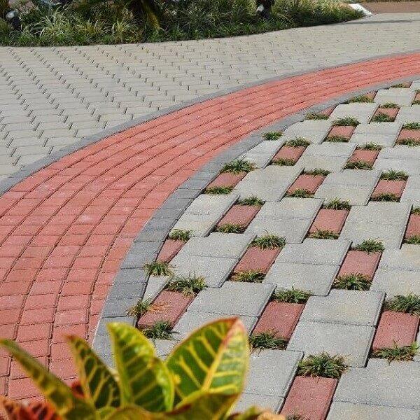 O piso intertravado vermelho forma lindas composições no chão da área externa com jardim. Fonte: Betonart Concretos