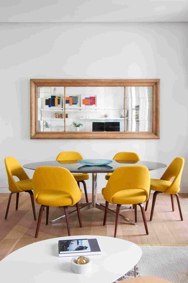 Parede com espelho na sala de jantar decorada com cadeira estofada amarela Foto Elle Decor