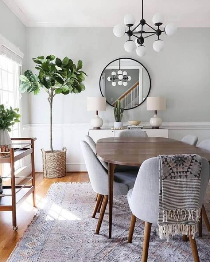Parede com espelho na sala de jantar decorada com lustre moderno e cadeiras estofadas Foto Apartment Therapy