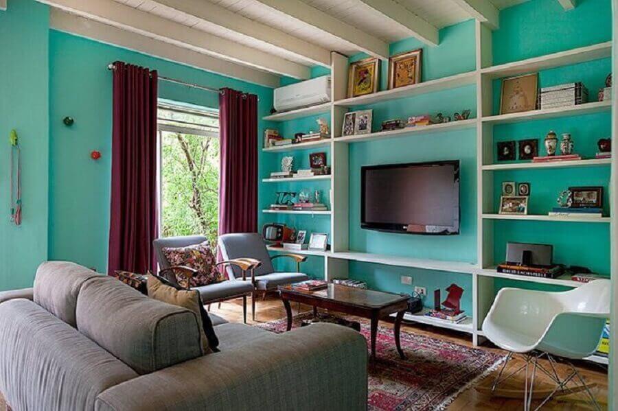 Parede cor ciano para sala de TV decorada com sofá cinza Foto Julia Ribeiro Fotografia