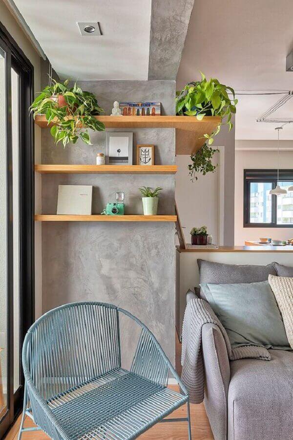 Parede de cimento queimado com prateleiras de madeira para decoração de sala com plantas Foto Voa Arquitetura