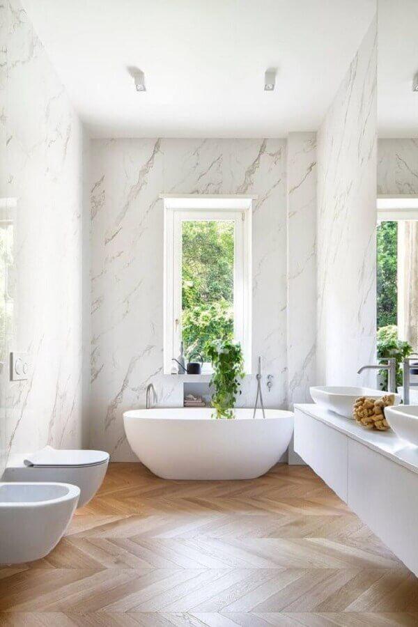 Parede de mármore para decoração de banheiro com piso de madeira e banheira de imersão Foto HomeAdore