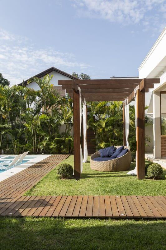 Pergolado de madeira com chaise área externa e piscina em frente