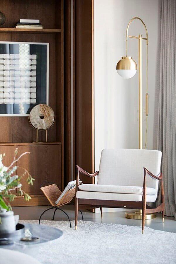 Poltrona decorativa branca para decoração de sala com luminária de piso e estante de madeira Foto Behance
