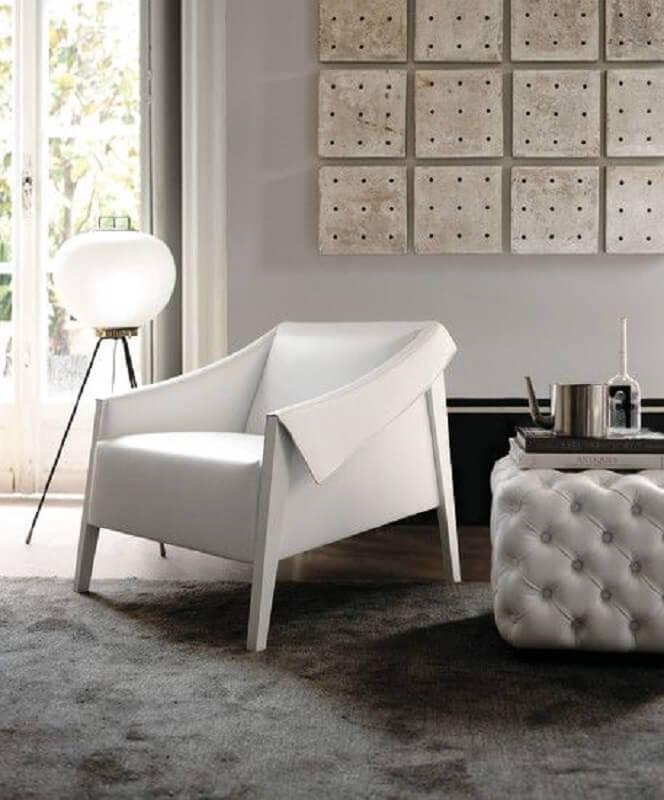 Poltrona branca moderna para sala decorada com puff capitonê e tapete cinza Foto HomeAdore