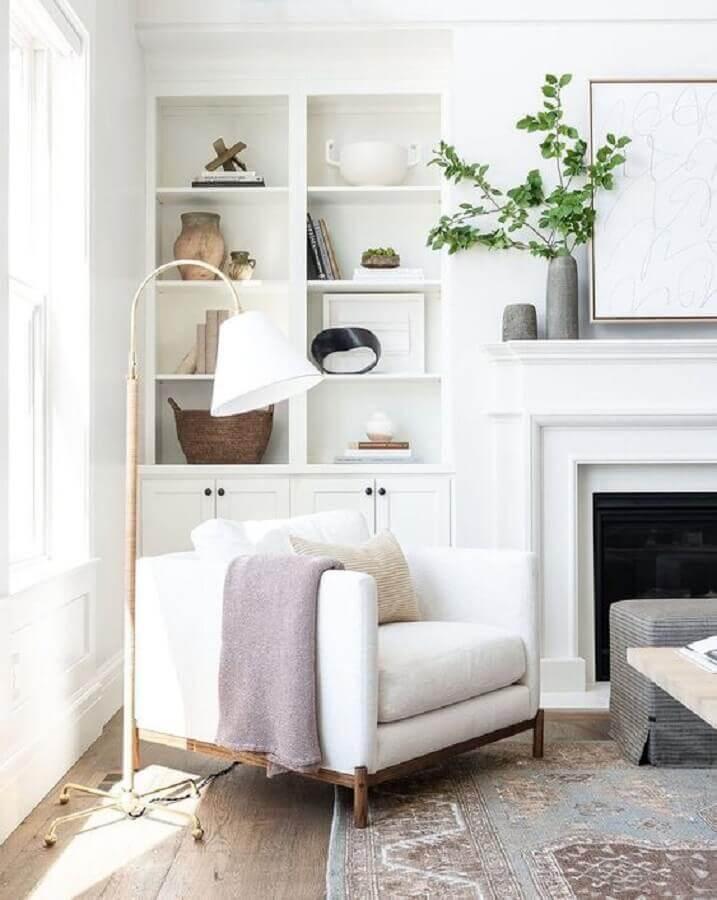 Poltrona branca para sala com lareira decorada com luminária de piso e estante planejada Foto McGee e Co.