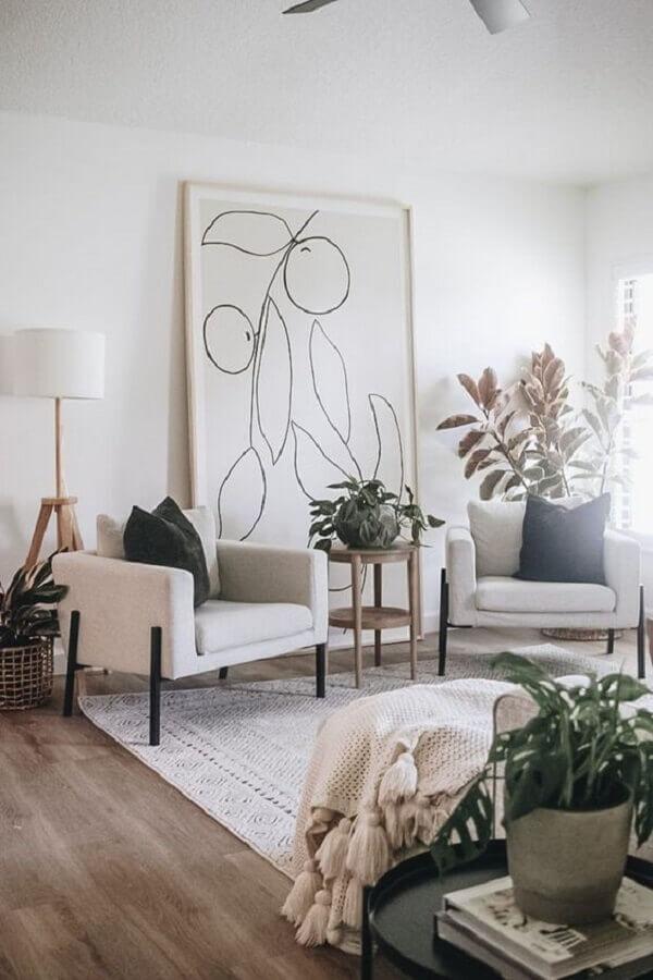 Poltrona branca para sala decorada com vasos de plantas e quadro grande Foto Casa Tres Chic