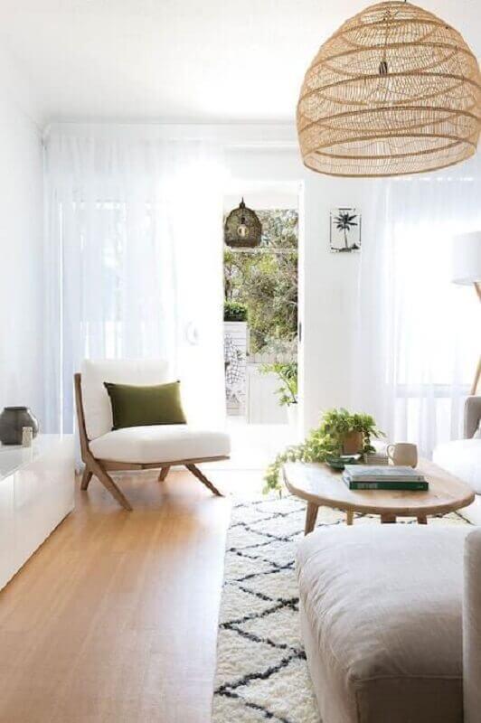 Poltrona branca para sala decorada em cores claras com lustre rustico Foto Apartment Therapy