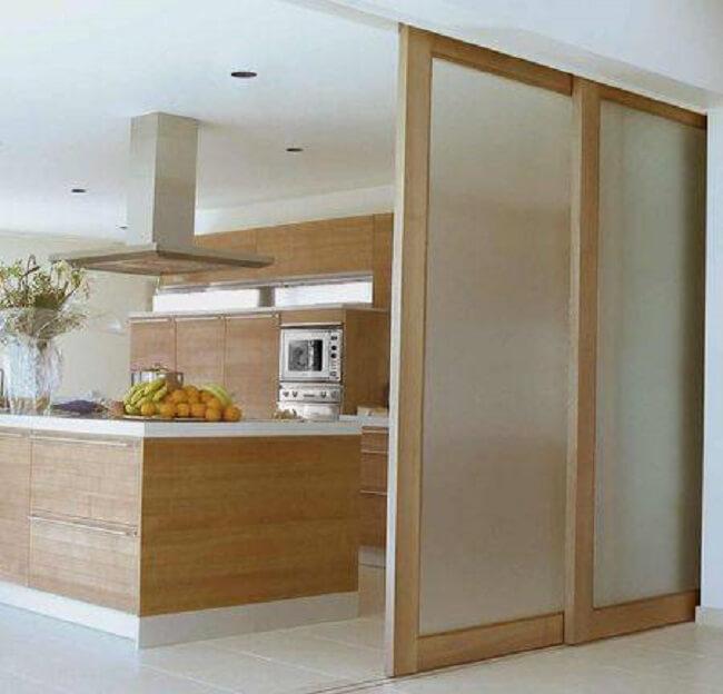Porta de madeira e vidro para sala camufla o ambiente da cozinha. Fonte: Arkpad