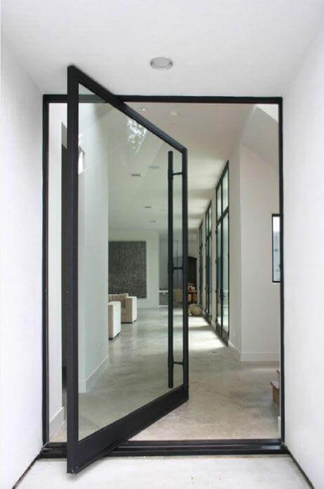 Porta de vidro para sala com design pivotante e estrutura de ferro preto. Fonte: Allen Bianchi Architects