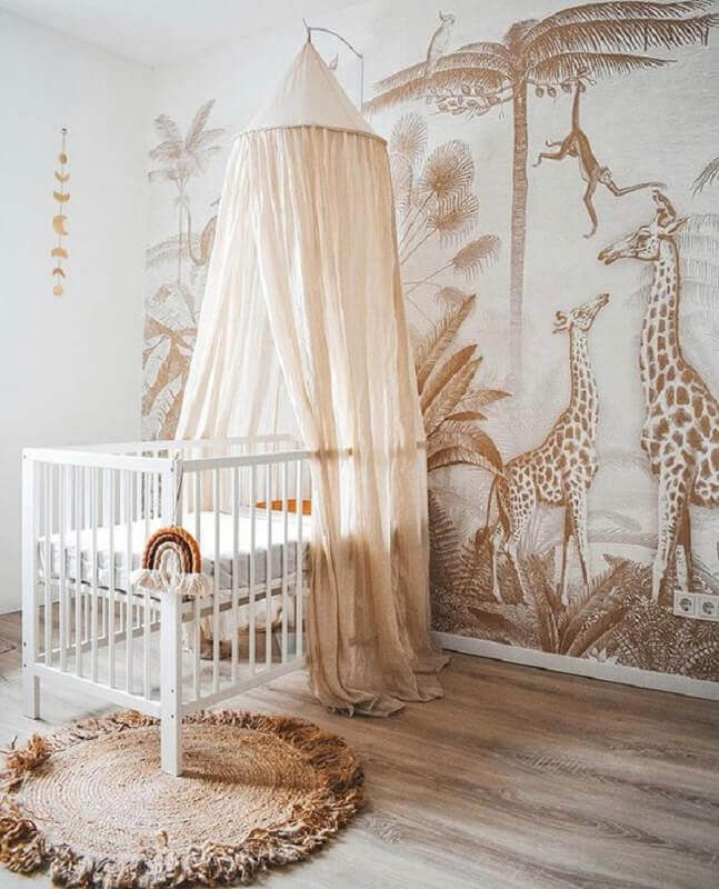 Quarto de bebê decorado em cores neutras com berço com dossel e papel de parede de animais Foto Kids Interiors