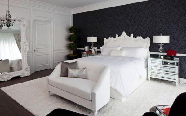 Quarto preto e branco com almofadas em tipos de cor prata e gabinete espelhado