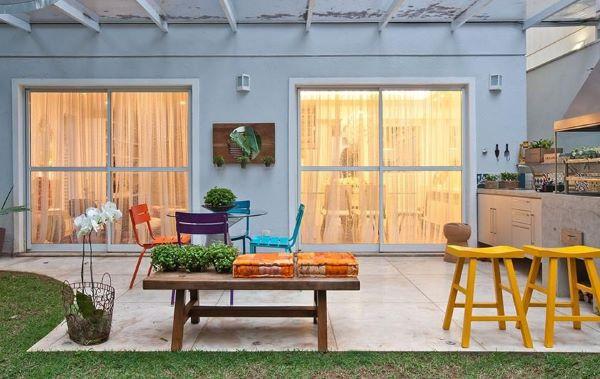 Quintal com churrasqueira a pequena moderna e moveis coloridos no espaço
