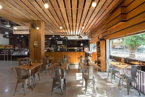 Restaurante com cadeiras na cor prata e mesas de madeira