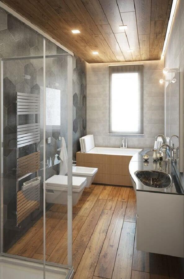Revestimento cinza hexagonal para decoração moderna de banheiro com piso de madeira Foto Voglia di Ristrutturare