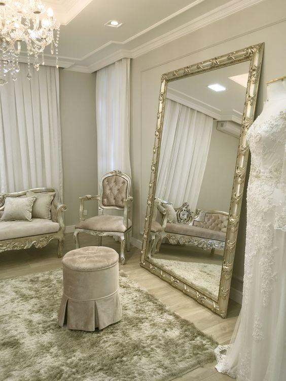 Sala clássica com espelho prata e moveis com detalhes na mesma cor