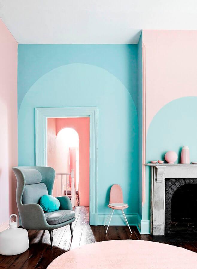 Sala com lareira decorada com parede cor ciano e detalhes em cor de rosa Foto Behance
