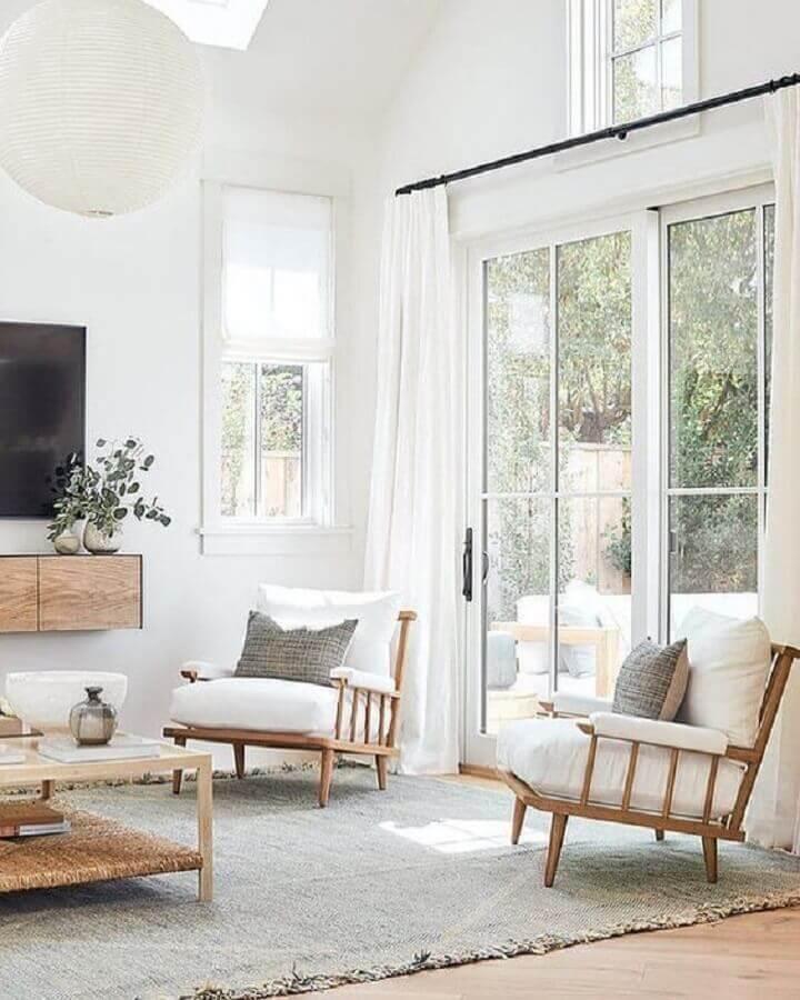 Sala de TV decorada com lustre redondo e poltrona branca com madeira Foto Studio McGee