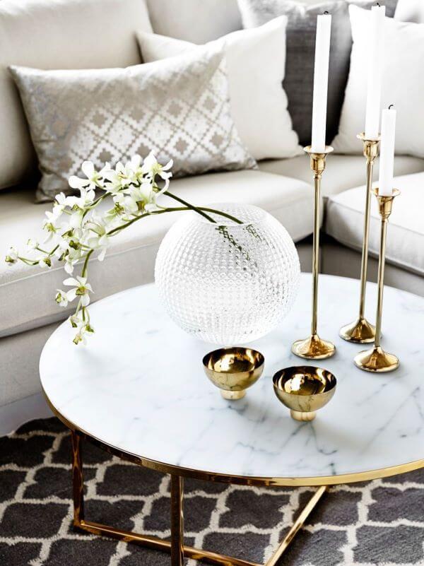 Sala de estar com almofadas na cor prata e moveis com dourado