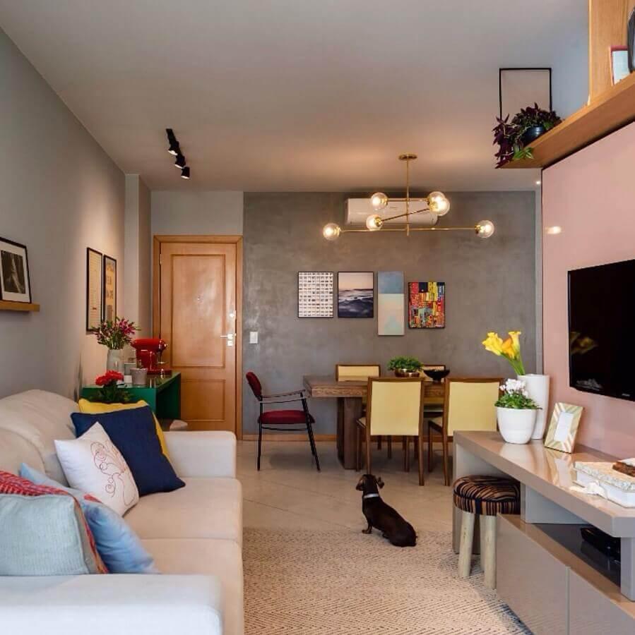 Sala de estar e jantar integrada decorada com parede de cimento queimado e lustre moderno Foto Decor Facil