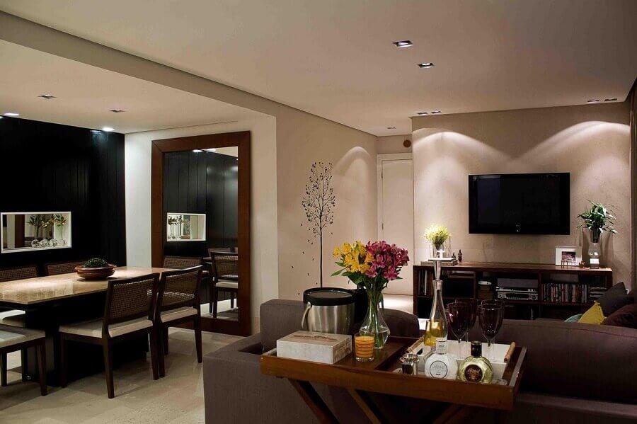 Sala de estar e jantar integrada decoradas com espelho de parede grande e aparador barzinho Foto Karen Pisacane