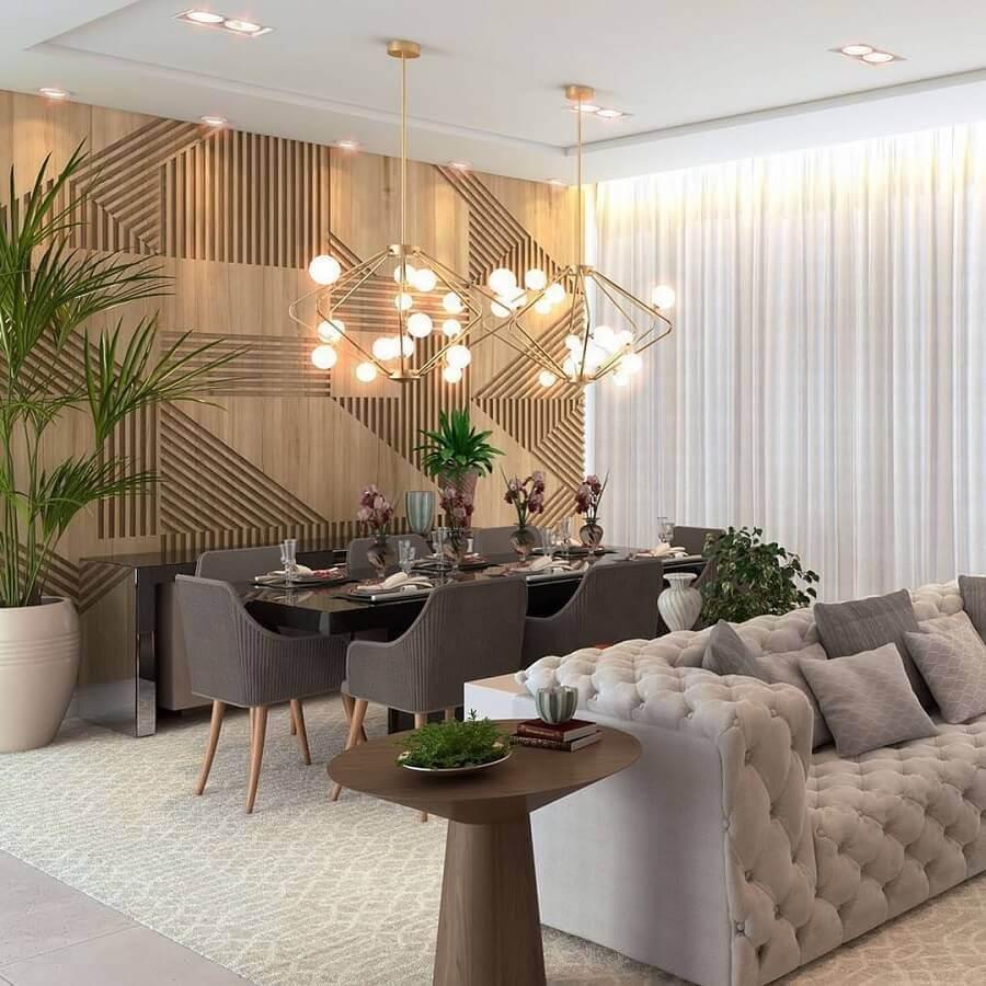 Sala de estar e jantar integradas modernas decoradas com sofá cinza capitonê e parede 3D de madeira Foto Katia Lopes