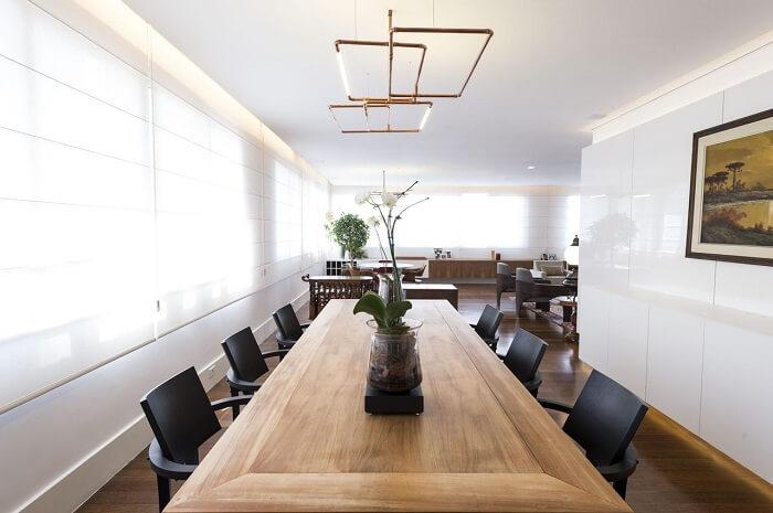 Sala de jantar de apartamento de luxo com mesa de madeira e cadeiras em tom preto. Fonte: Carla Cuono Arquitetura e Interiores