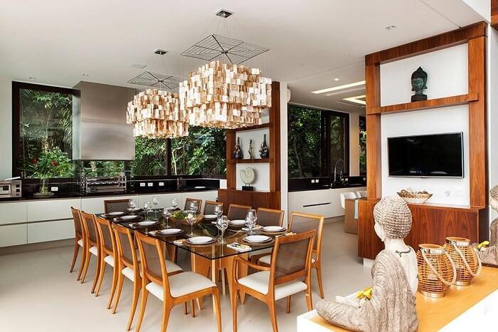 Sala de jantar de apartamento de luxo com mesa de vidro e cadeira de madeira. Fonte: Infinity Spaces