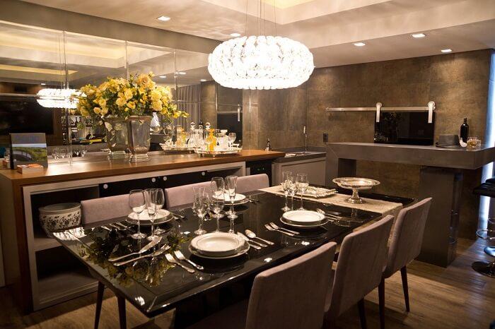 Sala de jantar de luxo moderna com mesa preta e cadeiras de veludo. Fonte: Oficina 802