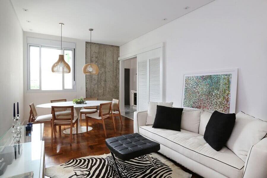 Sala de jantar e estar integradas decoradas com mesa redonda e sofá branco Foto Archduo Arquitetura