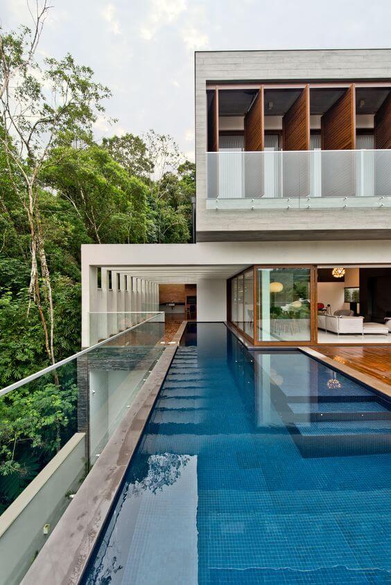 Sobrado com fachada de vidro e piscina retangular