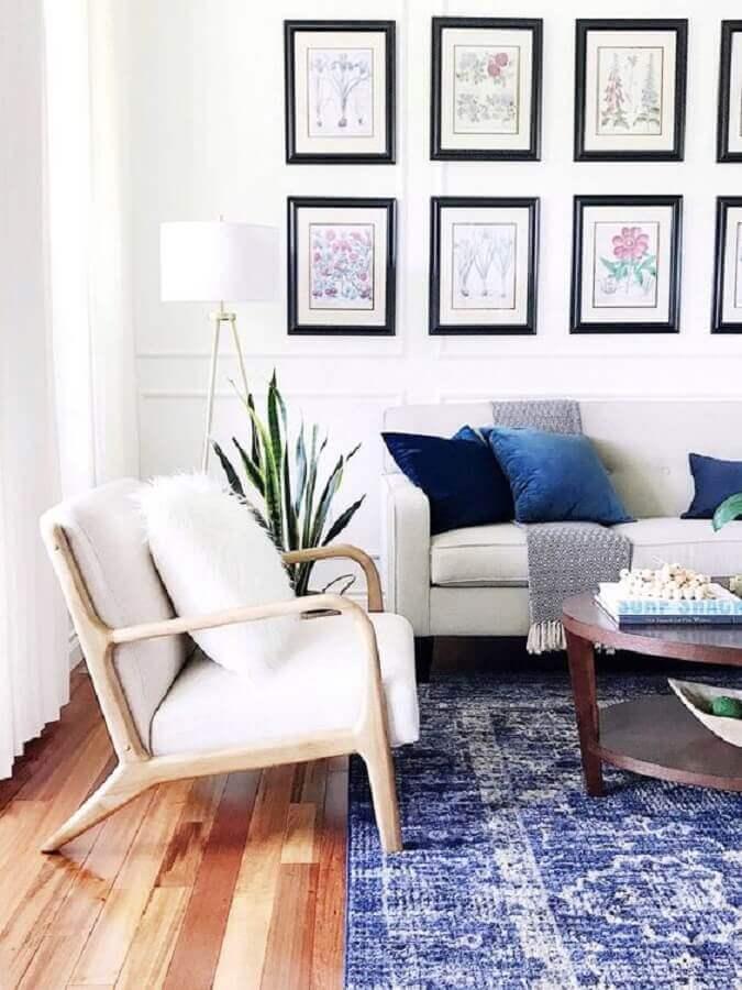 Sofá e poltrona branca para sala decorada com mural de quadros e almofadas azuis Foto Essential Home