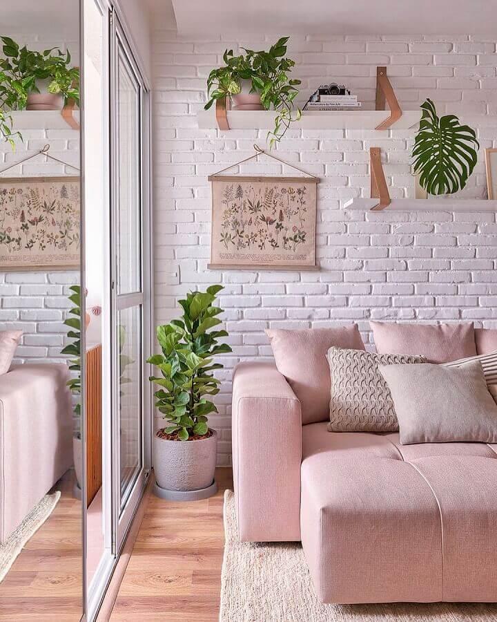 Sofá rosa para decoração de sala com plantas e parede tijolinho branco Foto Decor Fácil