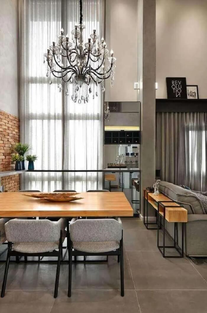 Vários elementos criam um espaço harmônico e uma decoração aconchegante para essa sala de jantar moderna e sofisticada com lustre e mesa de madeira. Fonte: Evolukit