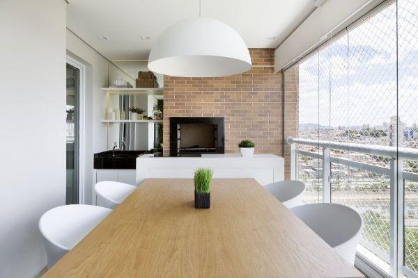 Varanda com churrasqueira pequena e mesa de madeira