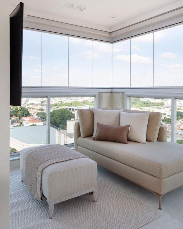 Varanda de vidro com chaise area externa longue e puff com manta chique