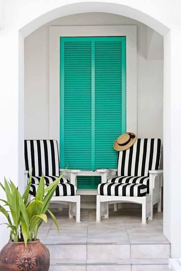 Varanda decorada com porta cor ciano e poltrona listrada Foto Home Fashion Trend
