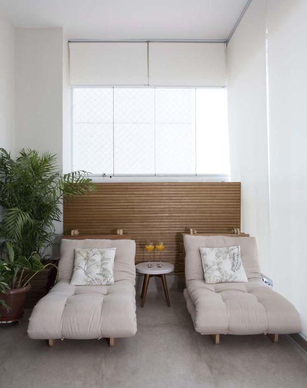 Varanda gourmet com conjunto de chaise área externa e vasos de plantas