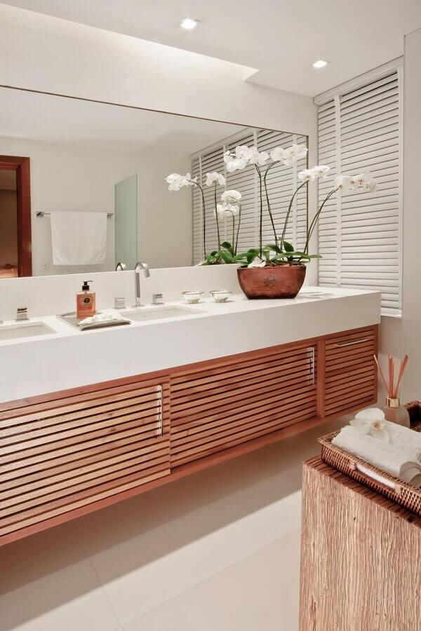 Vaso de flores para decoração de banheiro bonito branco com gabinete de madeira Foto Juliana Santana