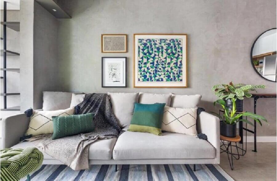 Vasos com plantas para decoração de sala com parede de cimento queimado e tapete listrado Foto Duda Senna