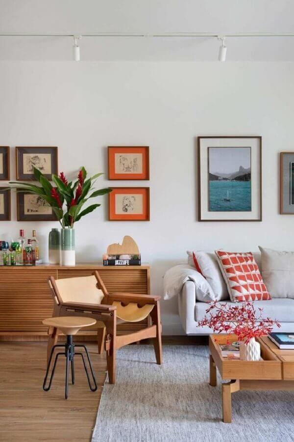 Vasos com plantas para decoração de sala de estar com poltrona de madeira e sofa cinza Foto Carmen Zaccaro Arquitetura
