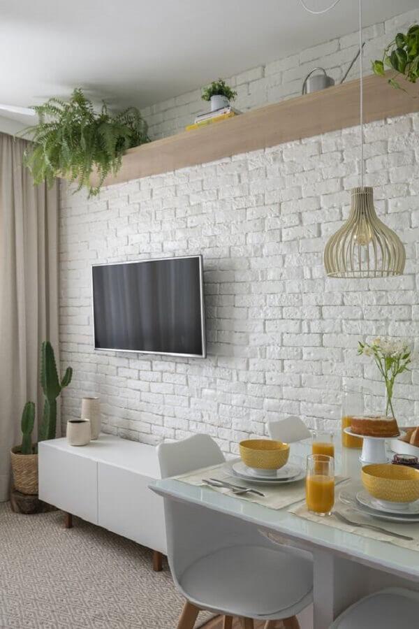 Vasos com plantas para decoração de sala de estar e jantar integradas com parede tijolinho branco Foto Casa Vogue