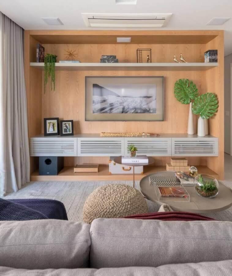 Vasos com plantas para decoração de sala em cores neuras com estante planejada de madeira Foto Dudi Duarte