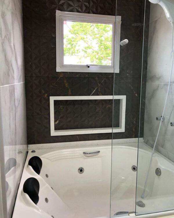 Banheira com nicho de porcelanato branco e preto