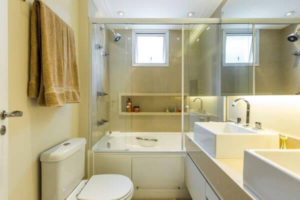 Banheiro com nicho de porcelanato na parede da banheira