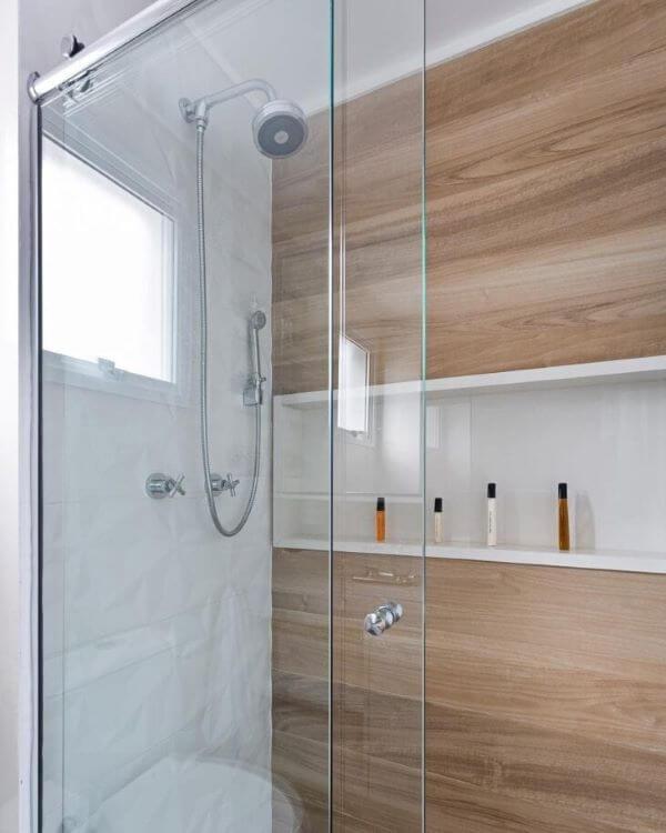 Banheiro com revestimento amadeirado e nicho de porcelanato branco