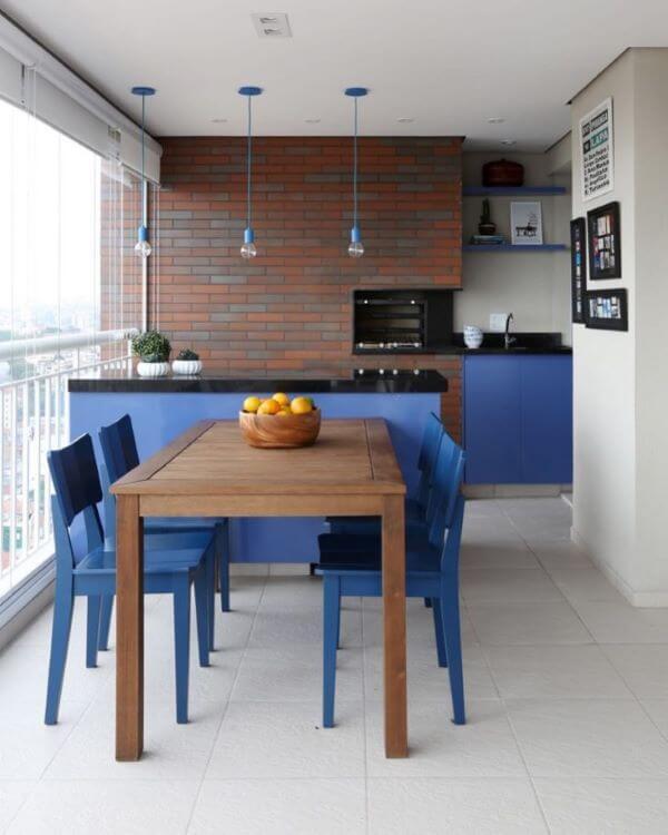 Cadeira para sacada azul e churrasqueira de tijolinho