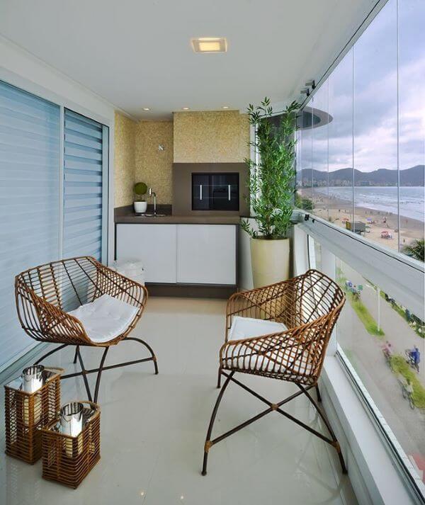 Cadeira para sacada de apartamento com plantas e cortina de vidro