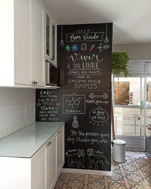 Cozinha com lettering na parede e armários brancos
