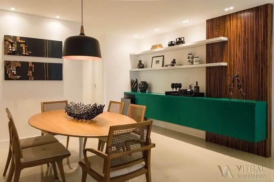 Decoração de sala de jantar com buffet suspenso verde e mesa de madeira redonda Foto Vitral Arquitetura